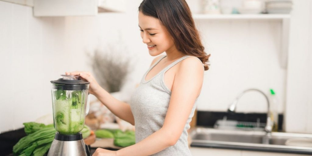 woman chopping vegetables in a blender