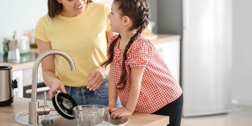 woman and child cleaning a blender in the kitchen